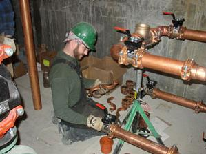 Plumber in North Miami Beach installs new copper piping in a warehouse